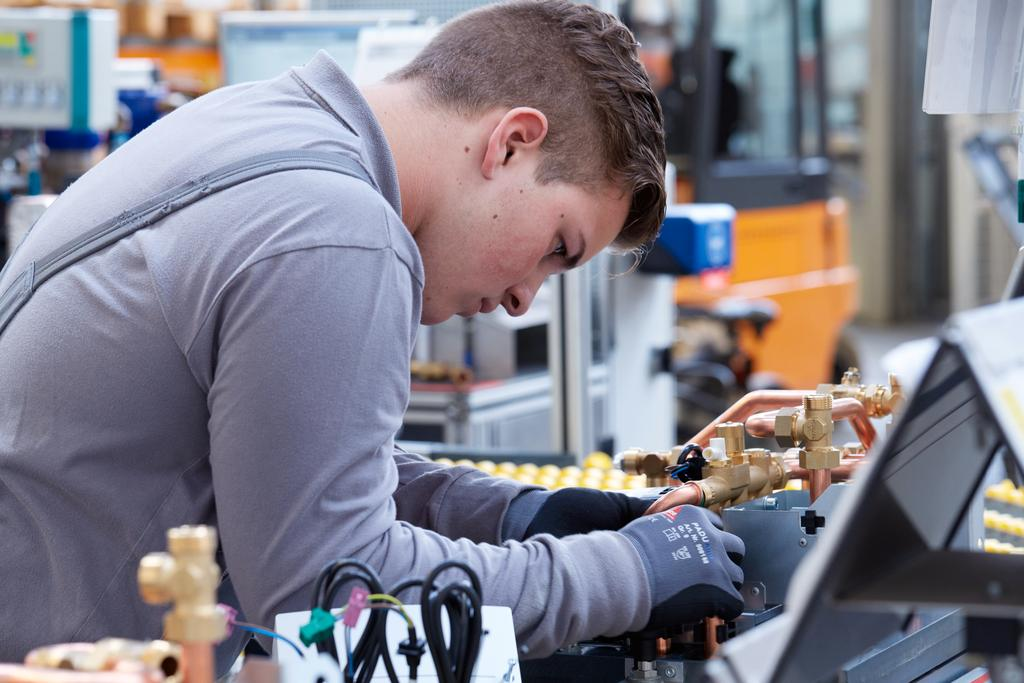 The image shows an apprentice in the technical department at Viessmann.