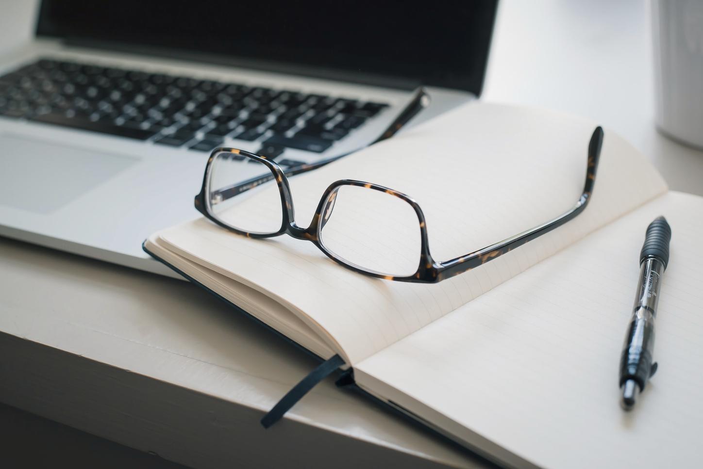 Das Bild zeigt eine Brille auf einem offenen Notizbuch, mit dem Laptop im Hintergrund