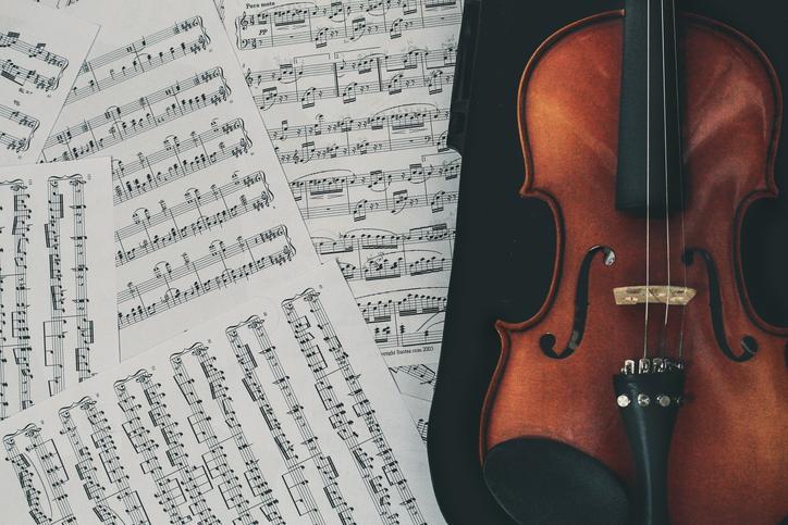 Das Bild zeigt Notenblätter und eine Geige.