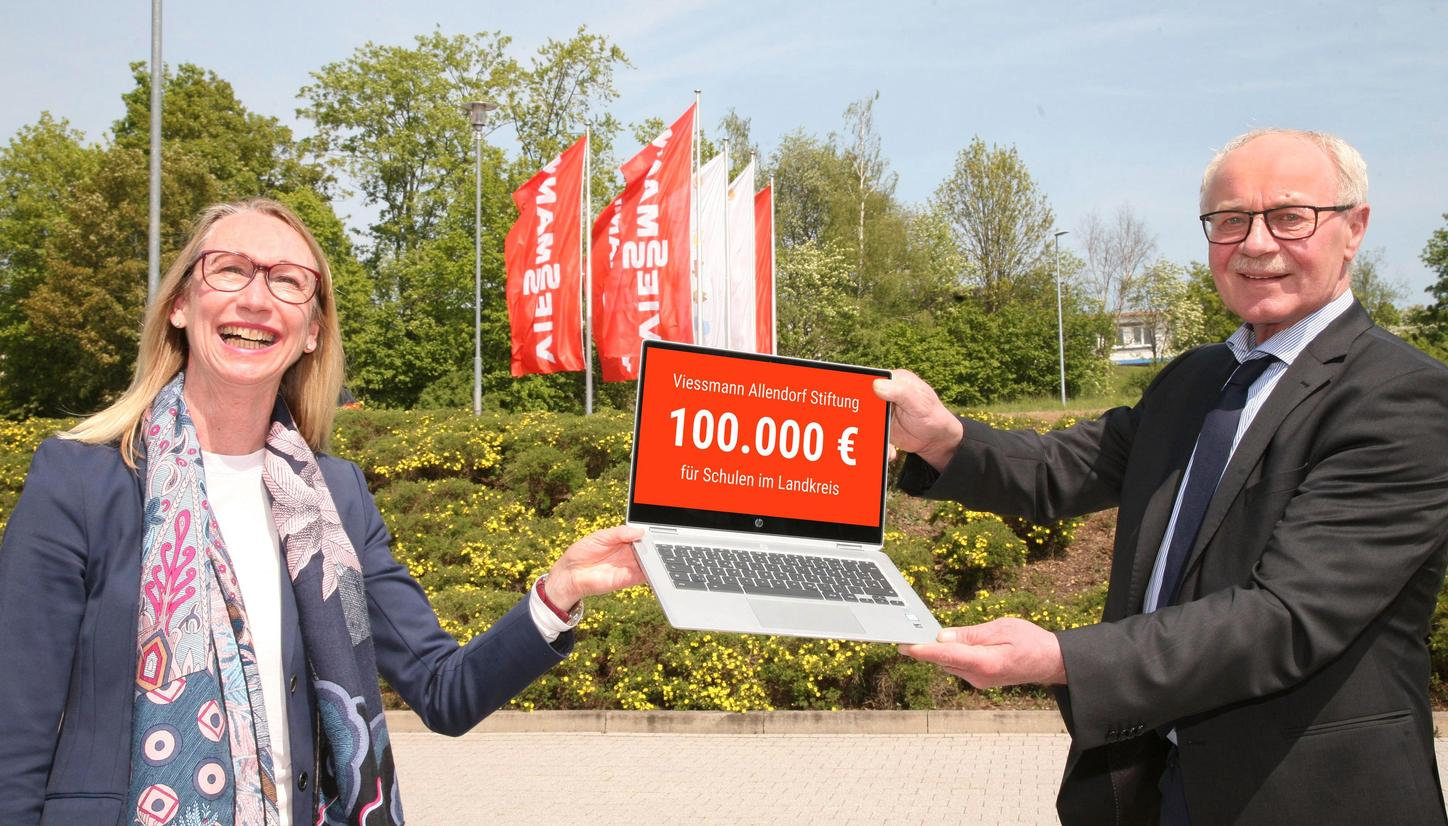 The image shows Annette Viessmann and Reinhard Kubat handing over a laptop.