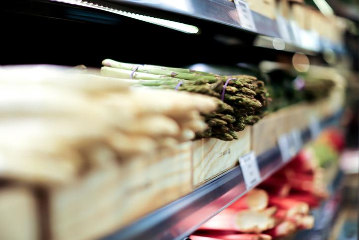 The picture shows a refrigerated shelf in a supermarket with fresh asparagus