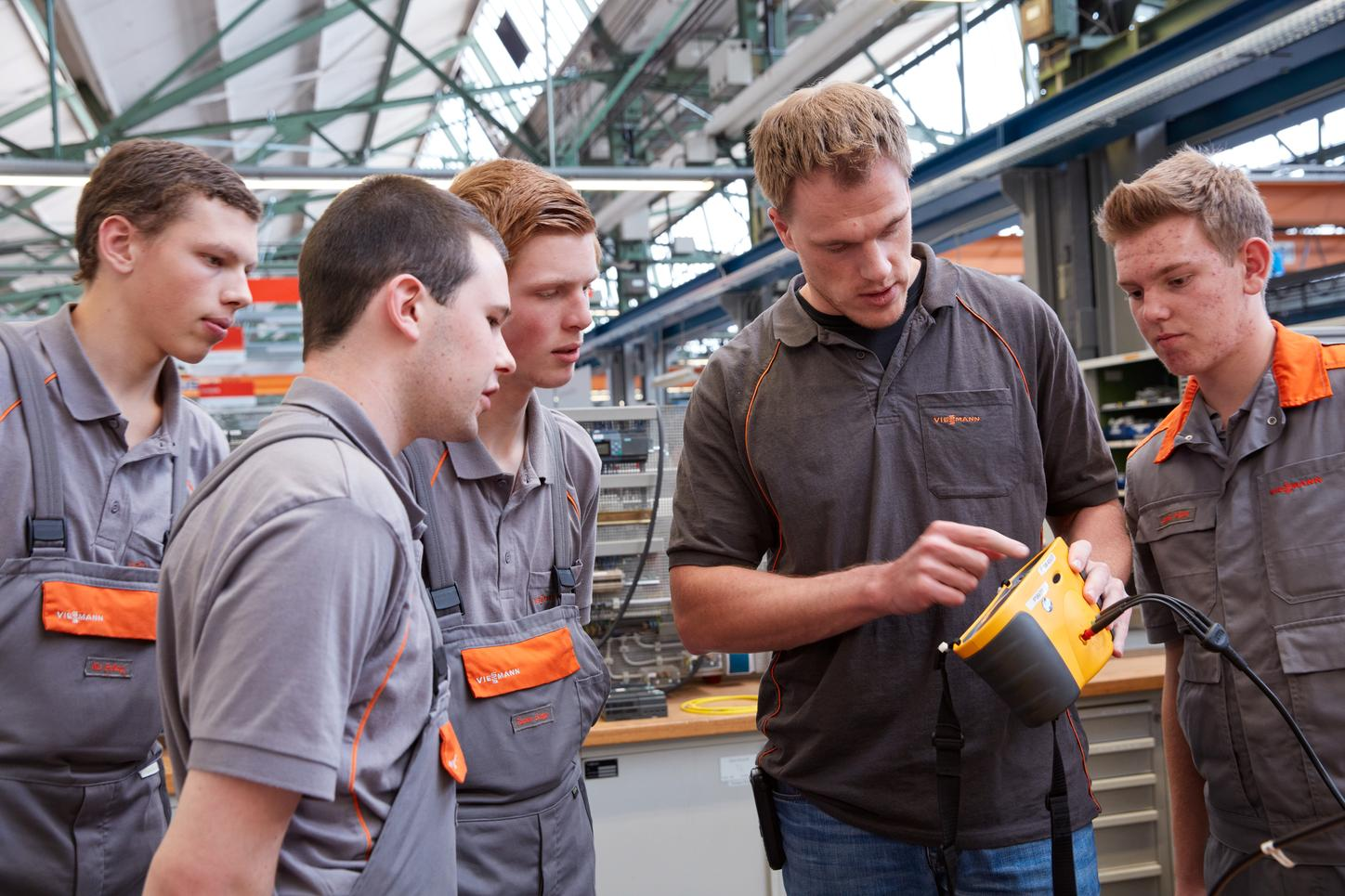 The image shows trainees at Viessmann, to whom an employee explains something.