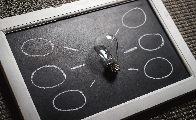 Das Bild zeigt eine Glühbirne auf einer Tafel als Symbol für das Ideenmanagement 2020