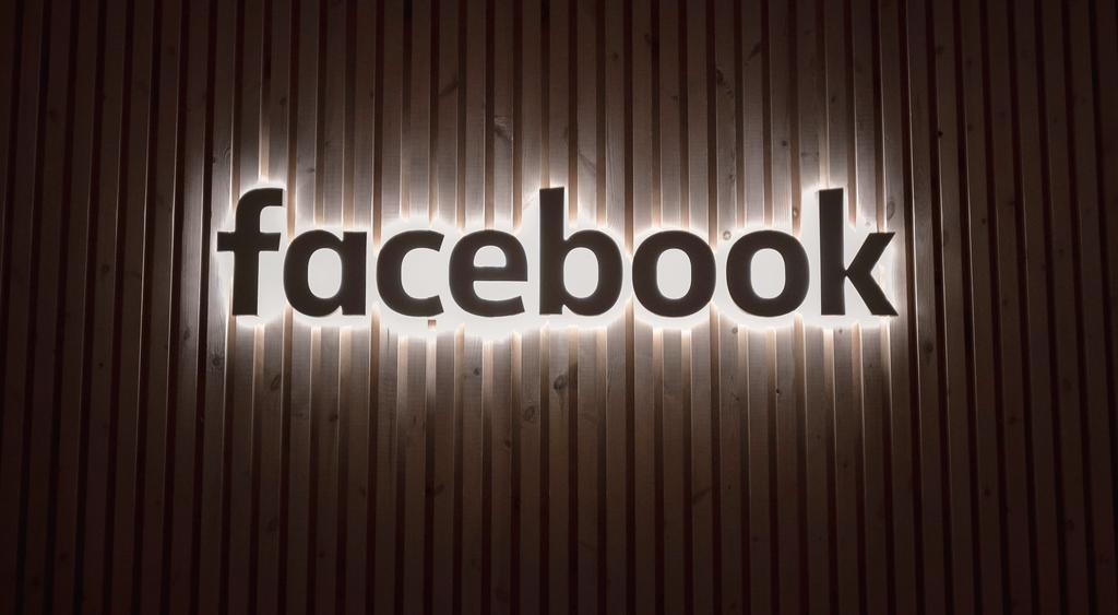 The image shows the illuminated Facebook logo.