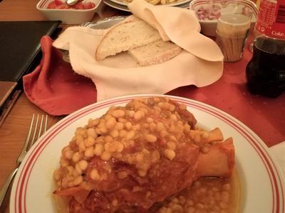 Wer könnte diese Mahlzeit problemlos essen? 800 Gramm geräucherte Schweinshaxe mit Bohneneintopf (Bild vorne). Das zweite Essen ist ein Schweinefilet, überbacken mit Käse und Schinken. Als Beilage werden Pommes serviert. Ort: Sibiu, Grande Plaza