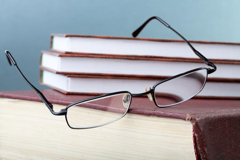 glasses hang down from a pile of books