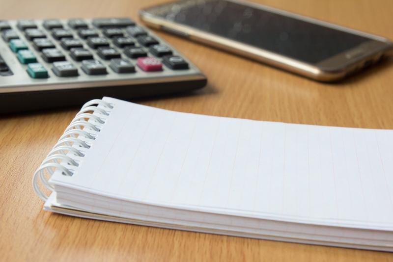Note paper, calculator and mobile phone on wooden table