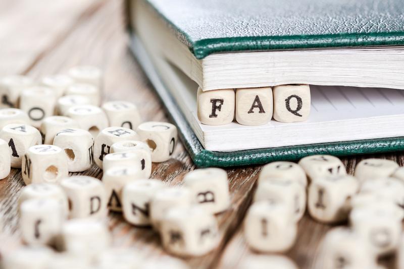 Word FAQ written on a wooden block.