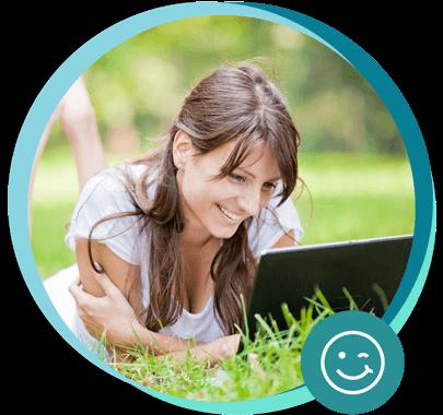 Frau im Gras mit Laptop