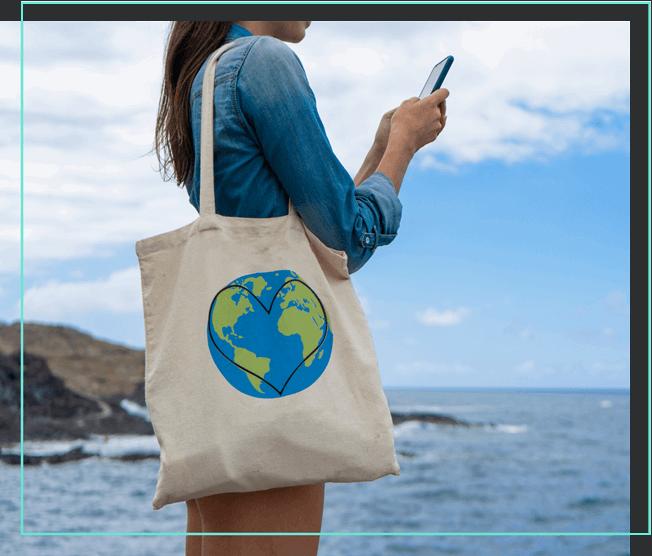 Frau mit Jutebeutel und Smartphone am Meer
