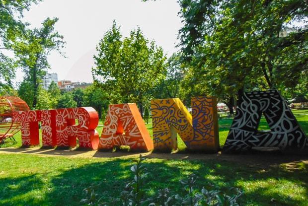 Parkanlage mit einem Kunstwerk in Form von großen Buchstaben, die das Wort Tirana bilden.