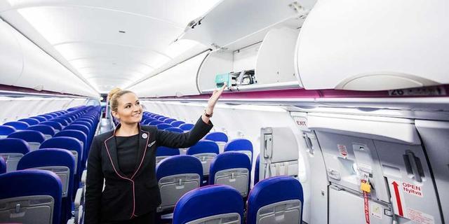 Flugbeleiterin an Bord eines Wizz Air-Flugzeugs zeigt das Fach für das Handgepäck.