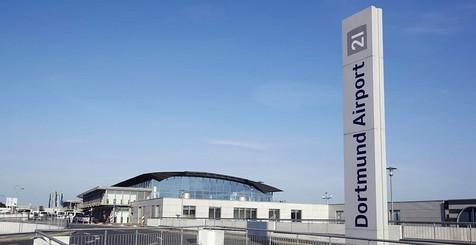 Stele mit Logo und Terminal des Dortmund Airport