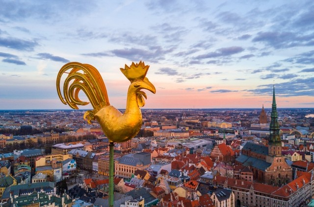 Golden cock on the top of the dome cathedral during sunset over riga beautiful wallpaper