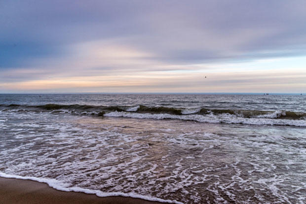 Sunset on gdansk beach in march. waves coming to shore.