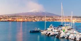 Skyline und Hafen von Catania auf Sizilien mit dem Vulkan Ätna im Hintergrund.
