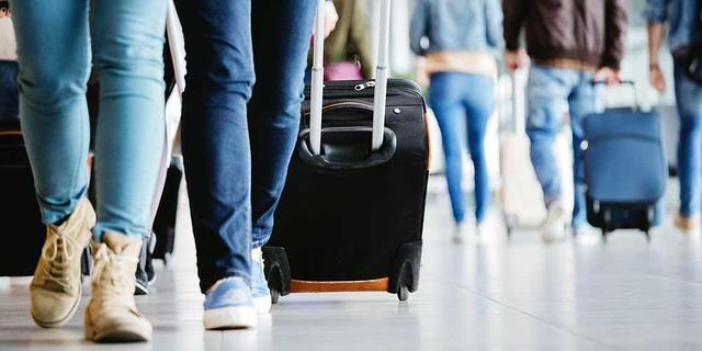 Passagiere mit Rollkoffern am Flughafen.