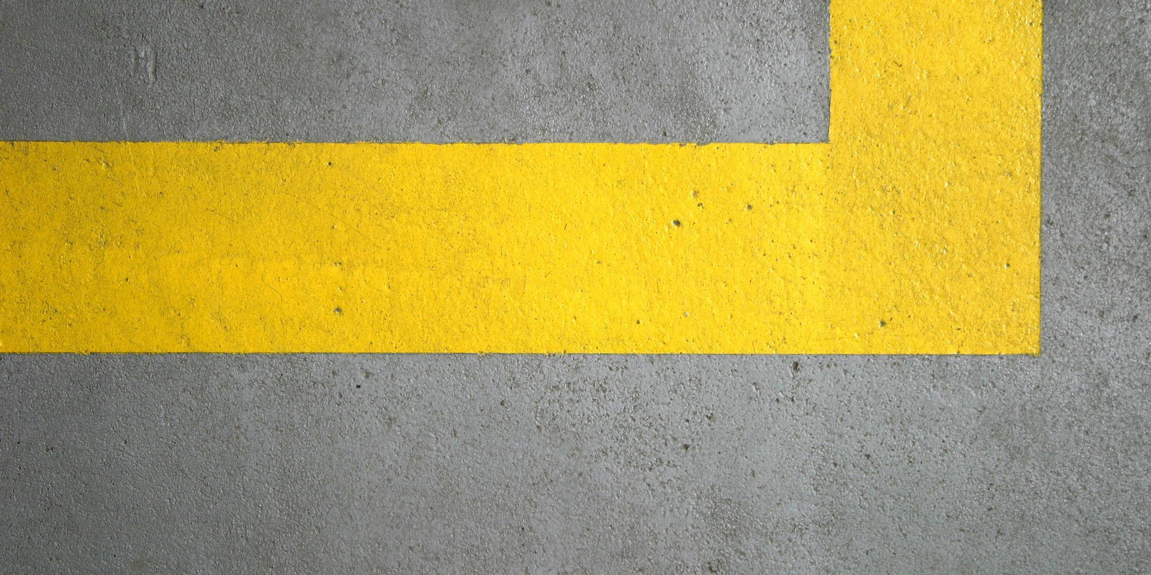 SAKRET International Lizenznehmer   gelb gestrichene Linie auf Betonuntergrund
