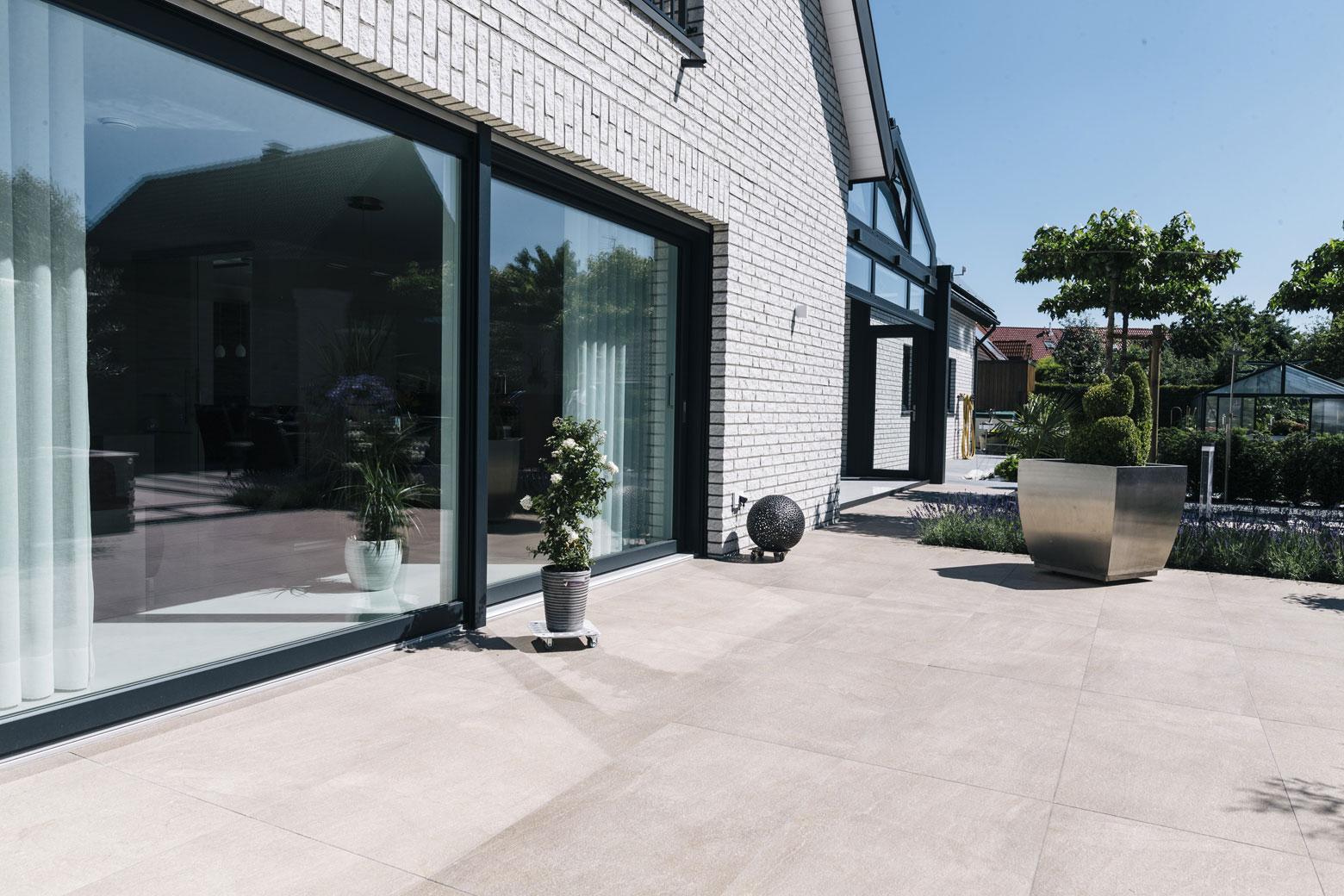 Terrasse mit Großformatplatten und breiter Fensterfront