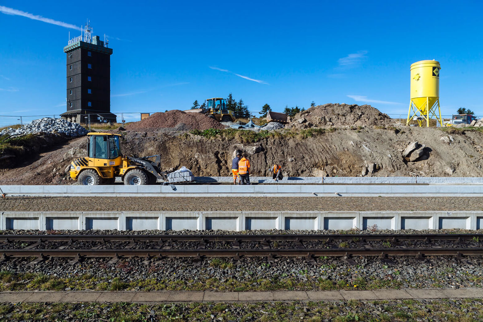 Bauarbeiten mit Bagger vor Hügel
