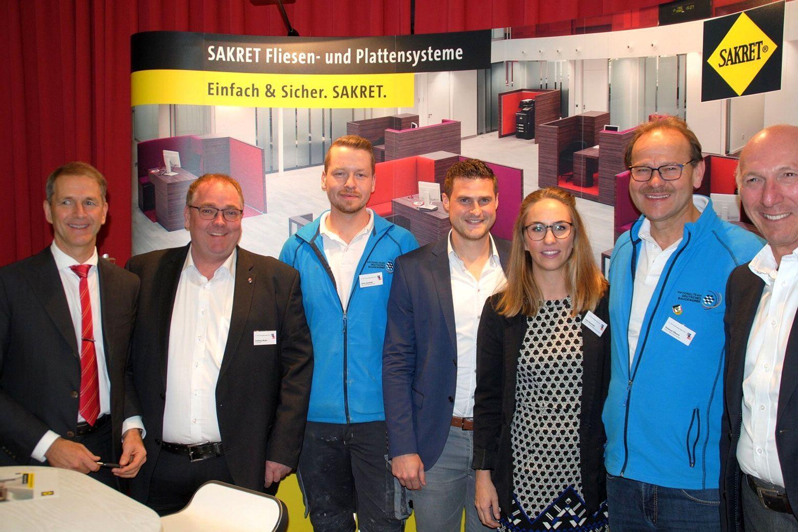 SAKRET-Mitarbeiter mit dem Fliesenlegerweltmeister Janis Gentner auf den 21. Sachverständigentage