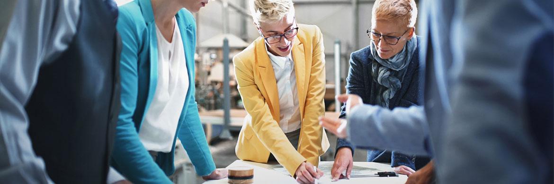 Unternehmer stehen um einen Tisch herum und diskutieren