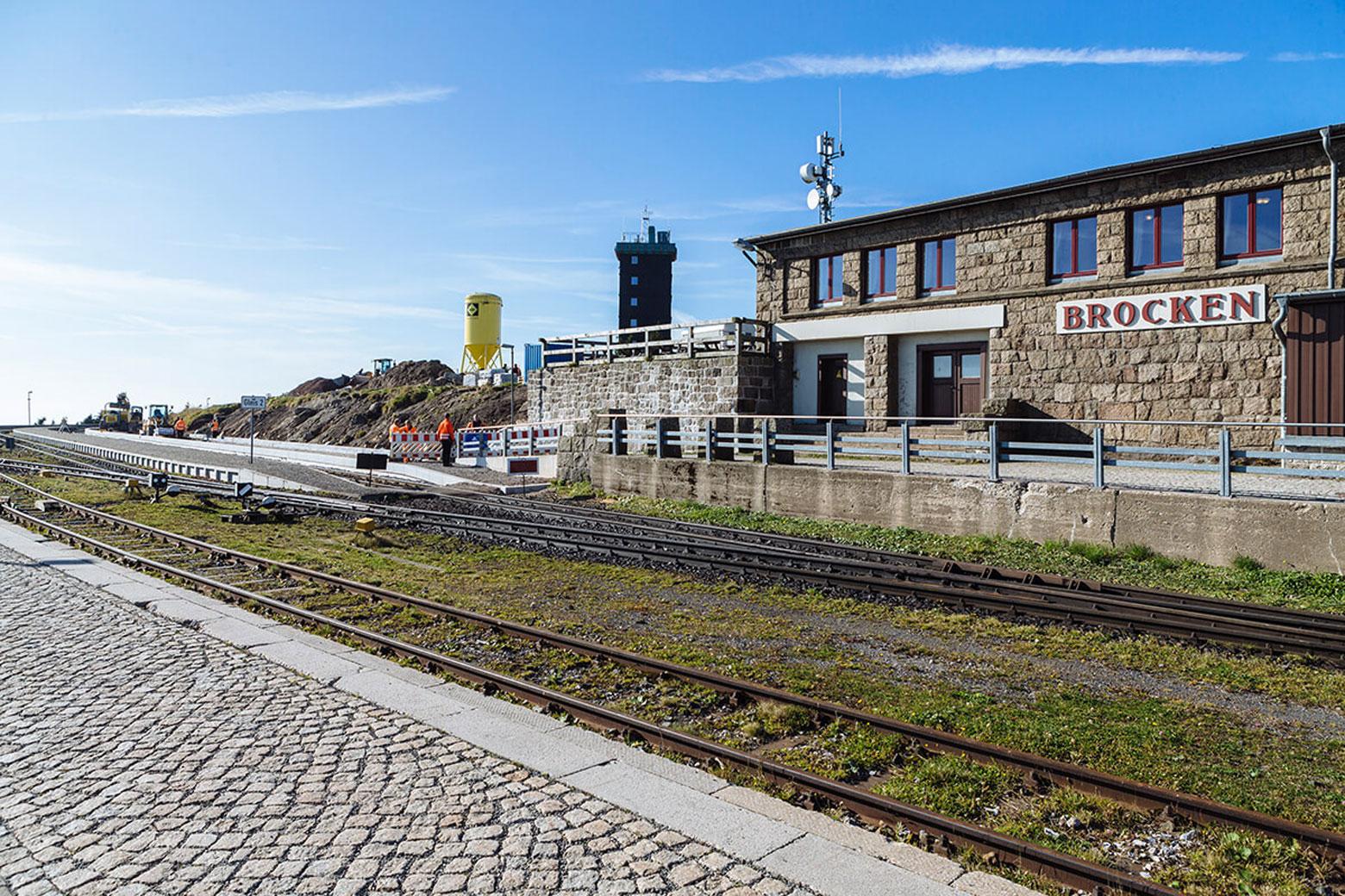Bahnsteig, Gleise und Verwaltungsgebäude vor klarem Himmel