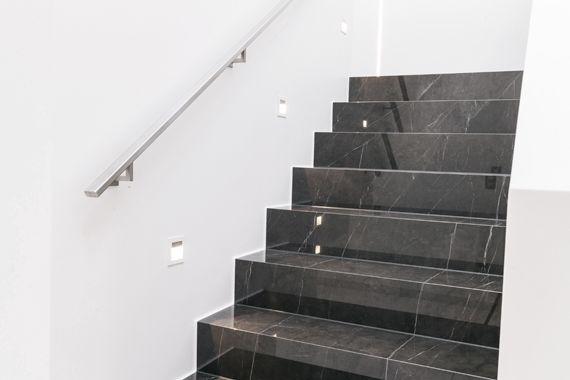 Geflieste Treppen mit Beleuchtung und Haltestange
