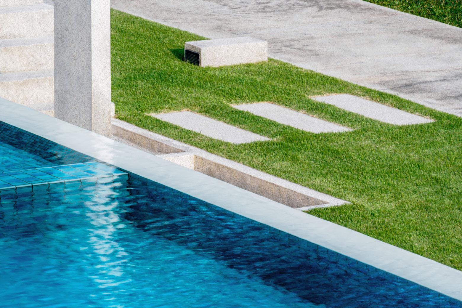 Schwimmbecken mit Rasen und Plattenweg