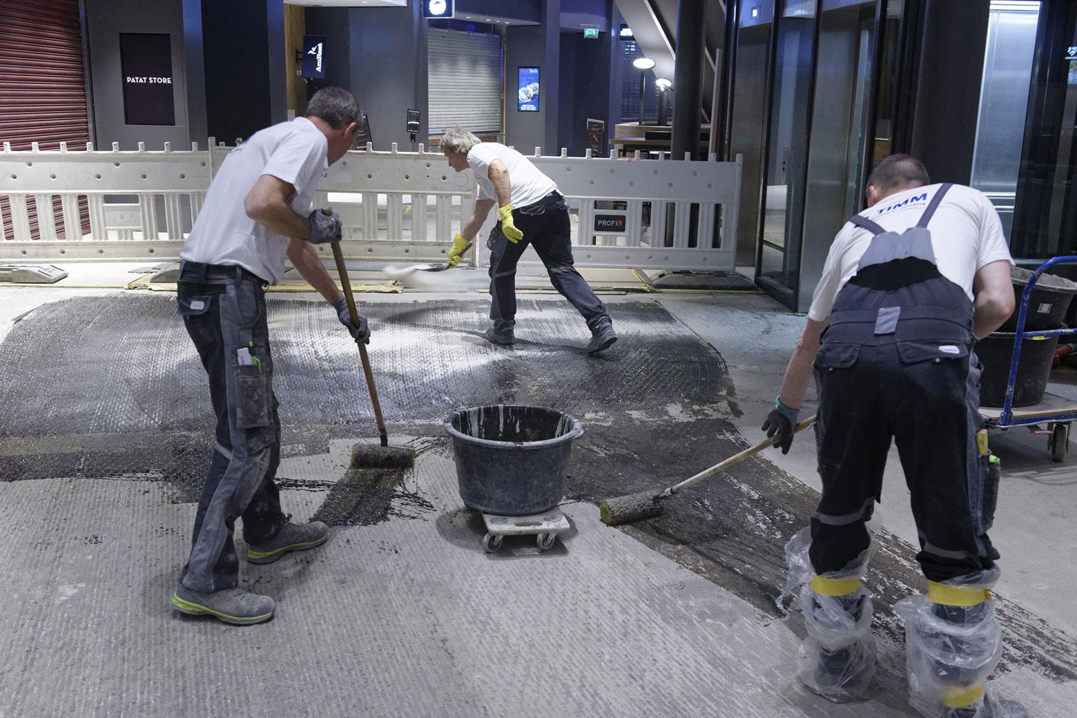 Nachtarbeit im Centro: Mitarbeiter von Timm Fliesen grundieren mit einer besonders schnell trocknenden Grundier- und Mörtelharzmasse.