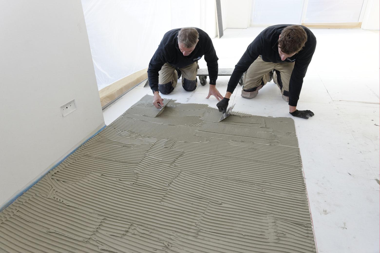 Fliesenverleger spachteln den Boden im Wohnzimmer mit Fliesenkleber