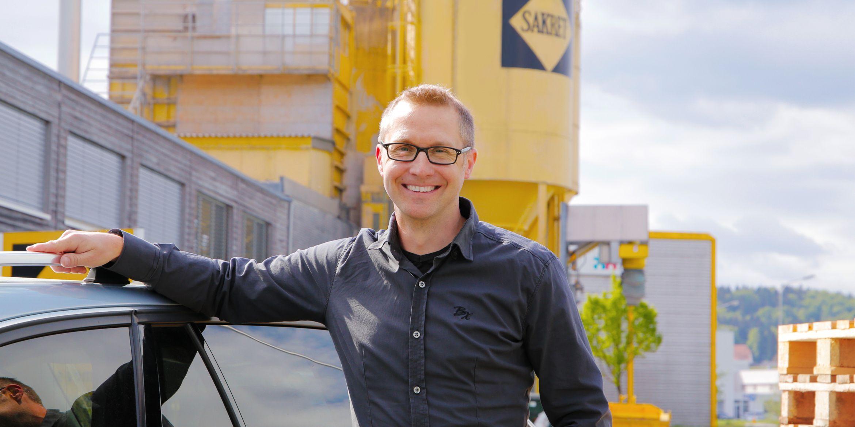 SAKRET-Mitarbeiter lehnt an Auto vor SAKRET Silos
