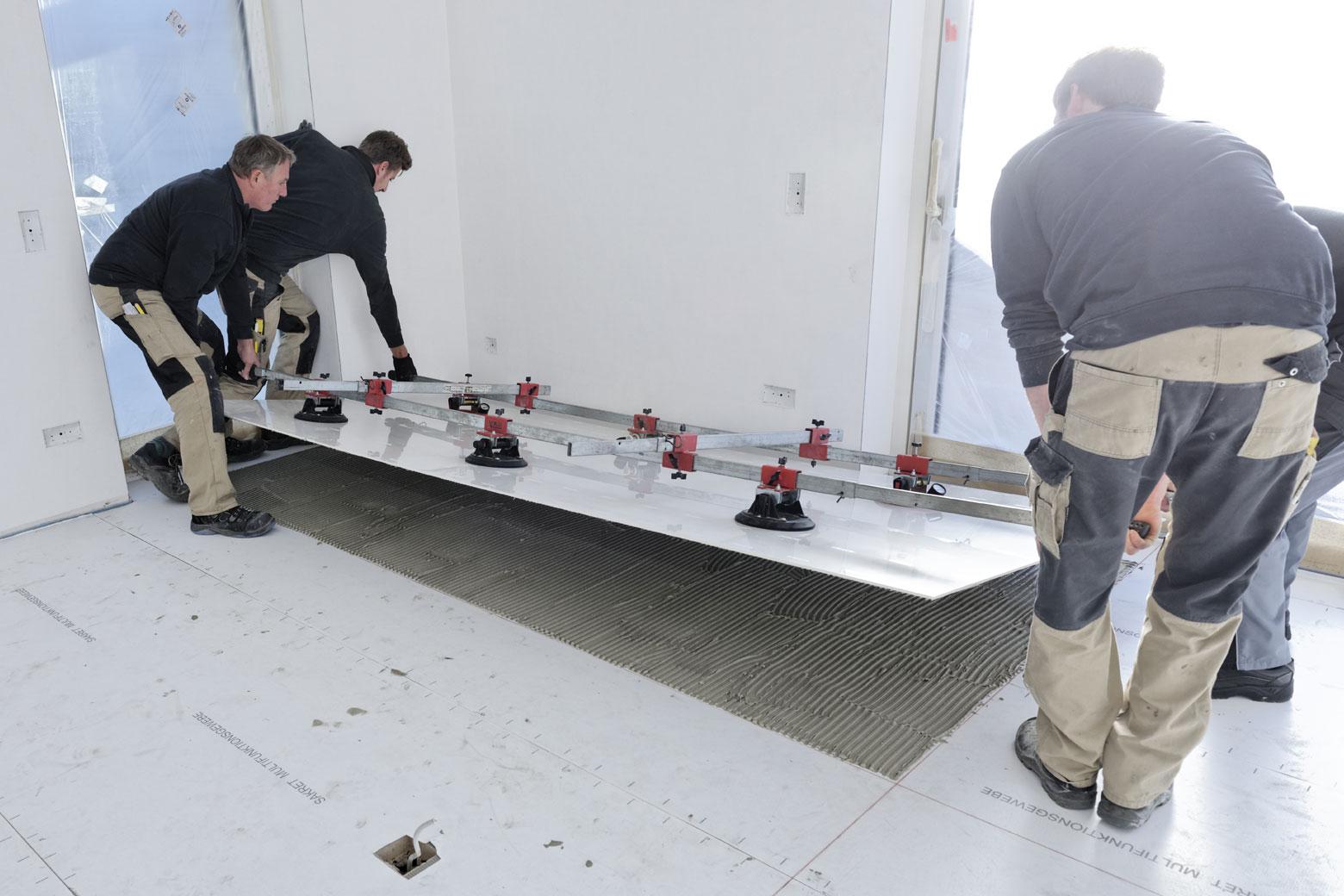 Fliesenleger setzen Großformat Fliese mit Spezialwerkzeug im Wohnzimmer ein