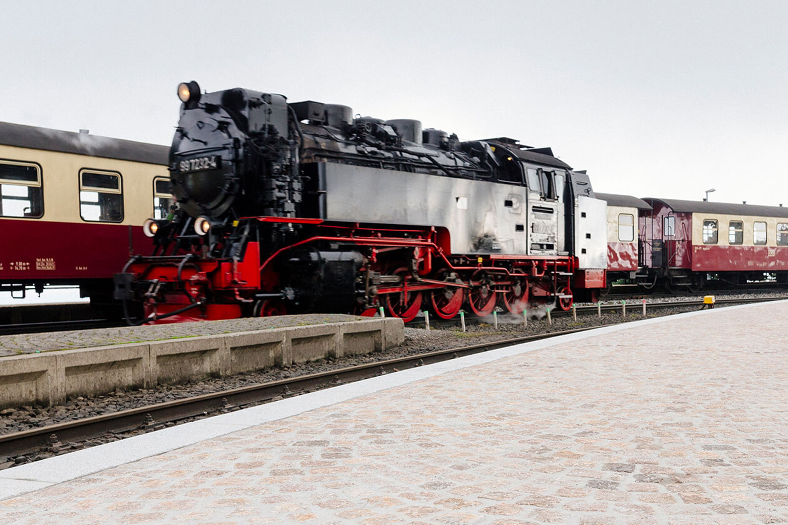 Einfahrende Lokomotive vor neuem Bahnsteig