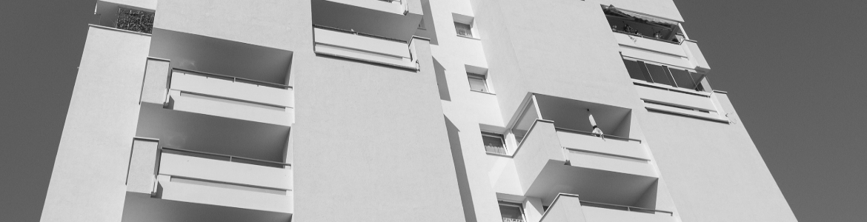 Bildausschnitt einer hell gestalteten Hochhausfassade mit Balkonen