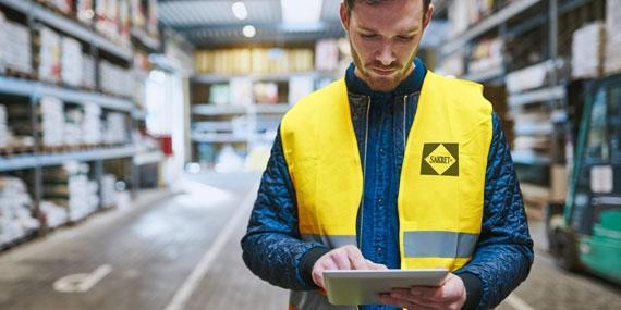 Informieren Sie sich über das Neuste aus der SAKRET Welt | Lagermitarbeiter mit Tablet