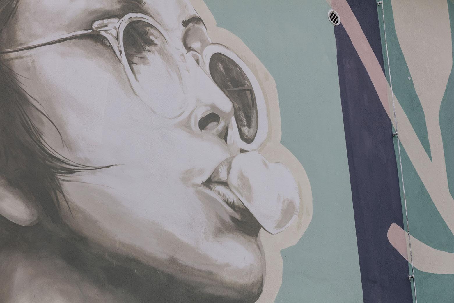 Graffiti-Kunst einer kaugummi-kauenden Frau an dem Filmhaus von Künstler Viktor Sobek