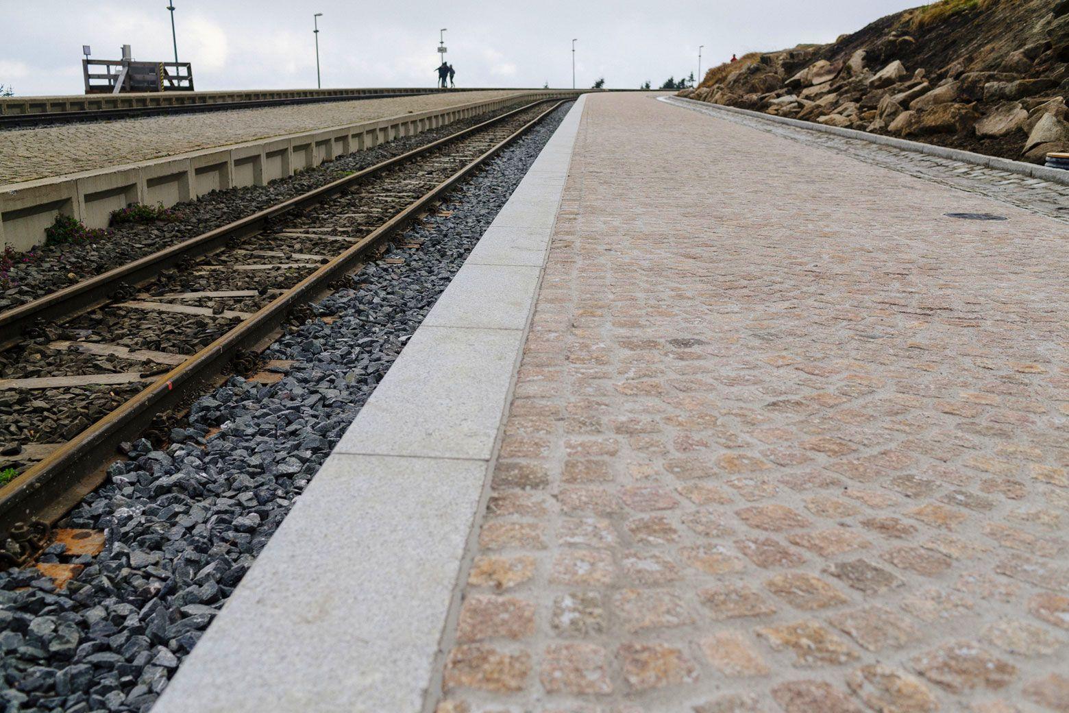 Ausblick über Bahnsteig und Gleise bei bewölktem Himmel