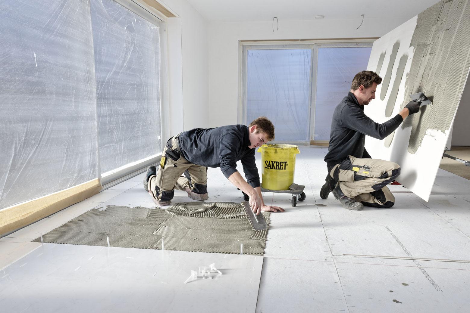Fliesenkleber wird auf Großformat Fliesen und Boden im Wohnzimmer aufgetragen