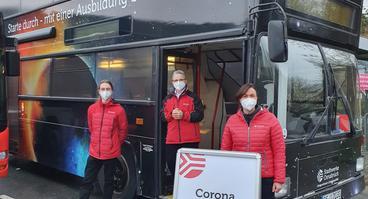 Freiwillige Stadtwerke-Mitarbeiter*innen vor der Corona-Schnellteststation im Dopperldeckerbus