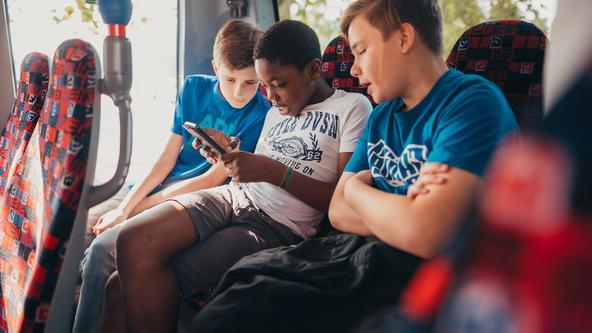 Drei Schüler sitzen nebeneinander im Bus