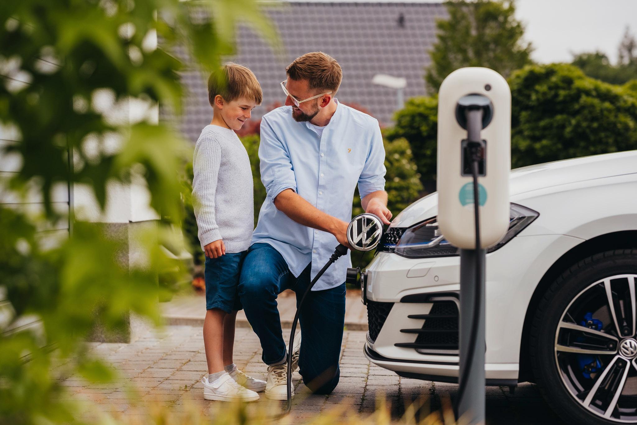 Mann mit Sohn vor Elektroauto. Mann lädt das E-Auto.