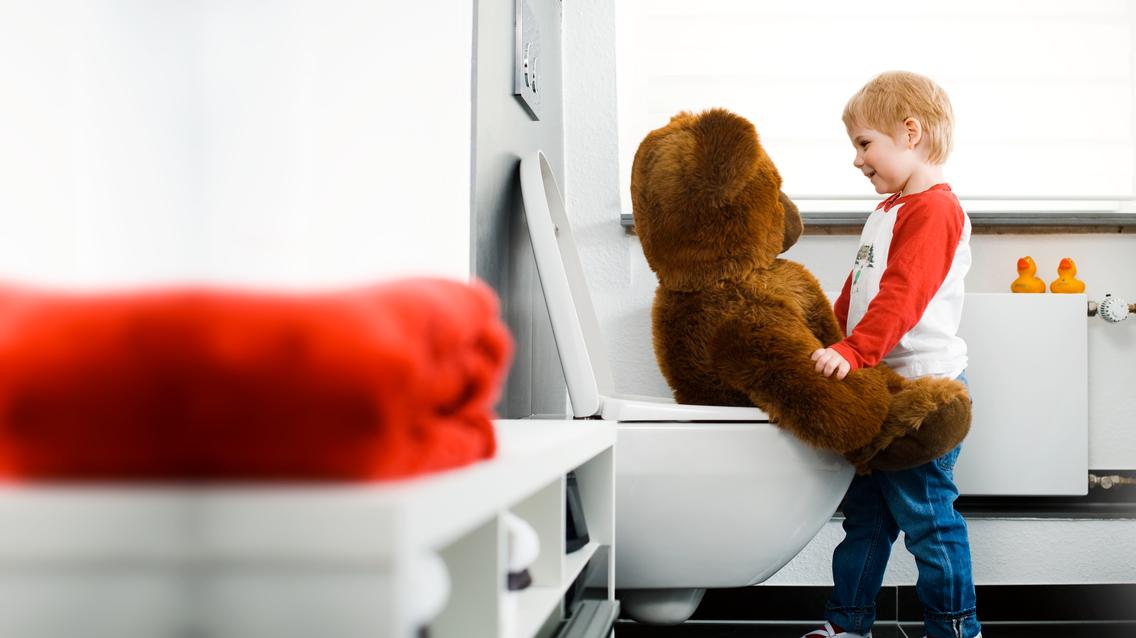 Kind mit Bär auf Toilette
