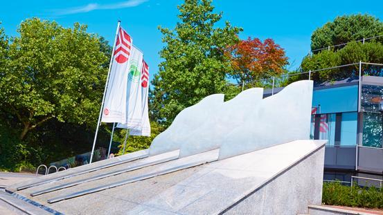 Eingang der Stadtwerke mit Wolkenbrunnen und Flaggen