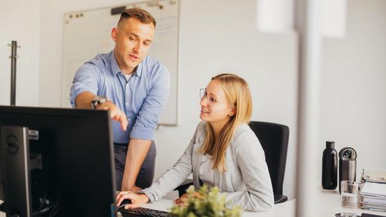 Student erklärt Studentin etwas am Computer im Büro