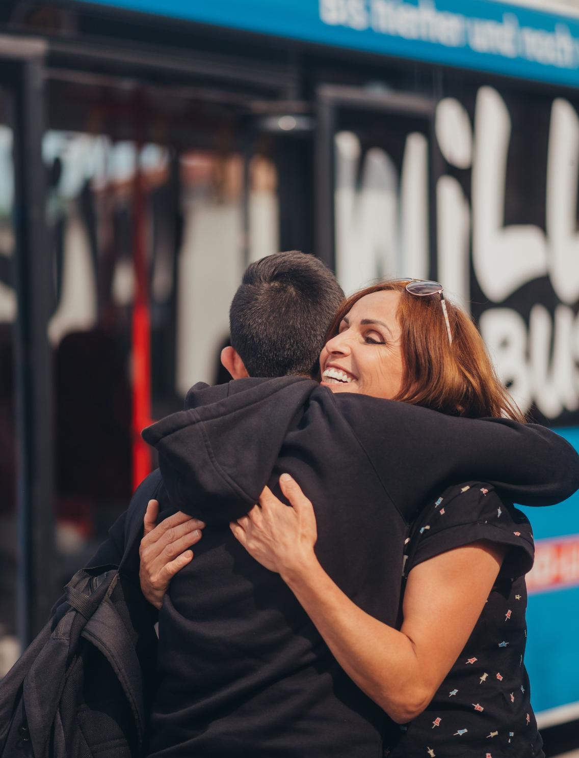 Mutter umarmt ihr Kind vor dem Bus der VOS
