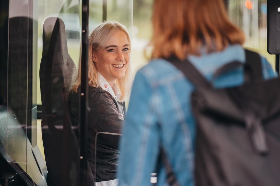 Busfahrerin begrüßt lachend einen Fahrgast