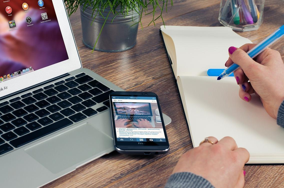 Junge Frau arbeitet mit Notebook, Handy und Block