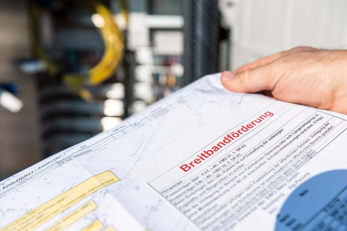 Ein Mitarbeiter zeigt einen Ausbauplan des geförderten Breitbandausbaus.