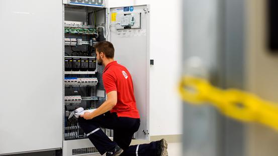Ein Mitarbeiter der SWO Netz GmbH sitzt vor einem Stromschaltkasten